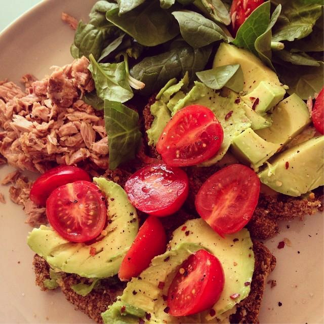 Avocado on Two Slices of Brown Bread Topped with Tomatoes, Spinach and a Side Portion of Tuna.